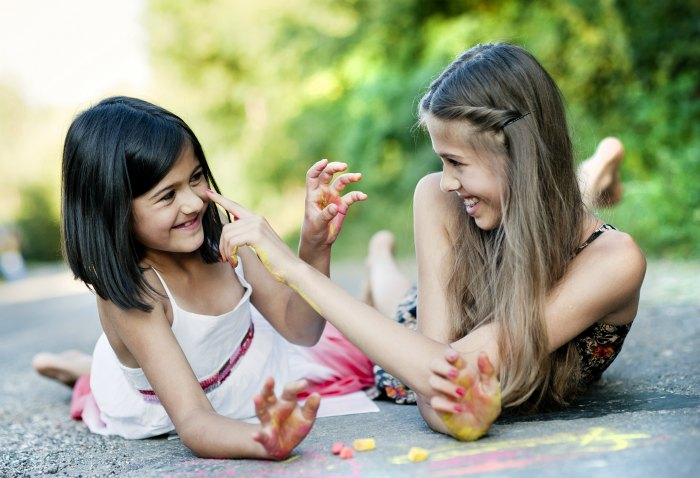 childhood friends playing with chalk