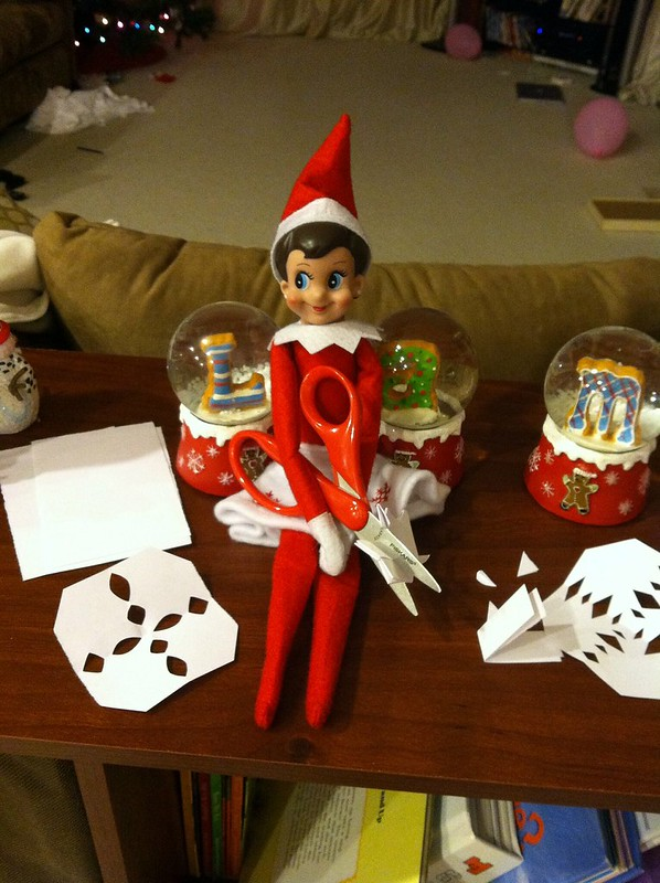 Elf on the Shelf making paper snowflakes