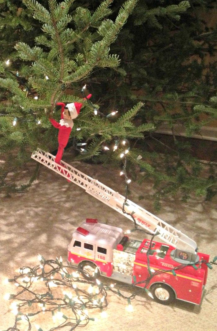 Putting Up Christmas Lights with a Firetruck onto the Christmas Tree - Elf on the Shelf | Mommy Evolution #elfontheshelfideas #elfontheshelf