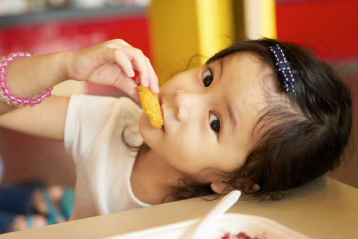 Little girl eating fast food chicken nuggets