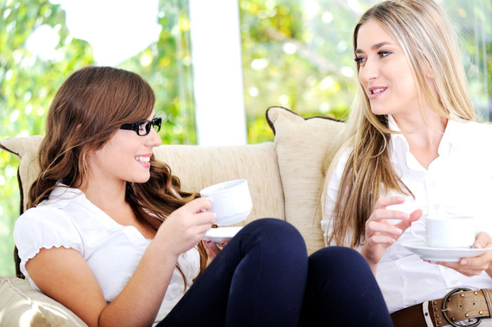 Two friends have a good time in sunny cafe coffee